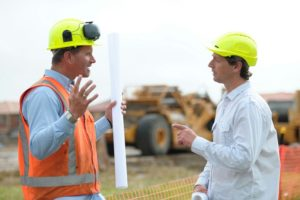 Two workers discussing construction plan