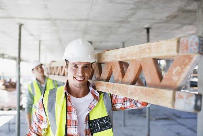 Construction worker carrying girder on construction site comp