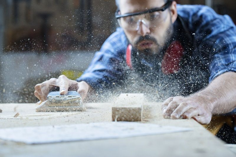 Young handosme carpenter blowing off sawdust art1 L com