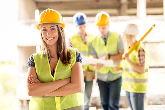 A woman builder in front of other builders