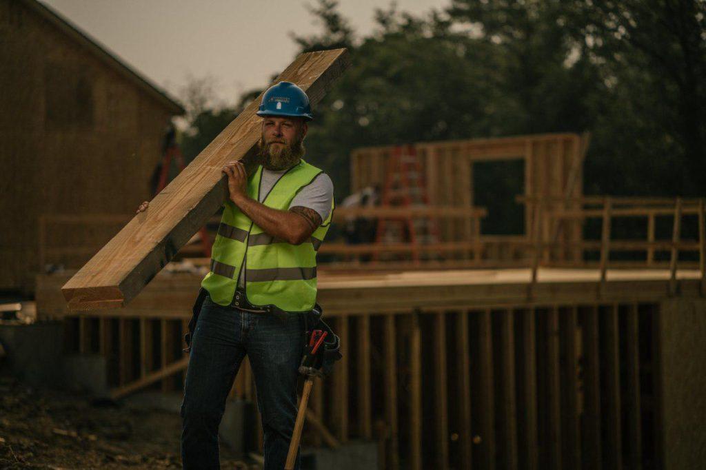 A craftsman dragging a timber