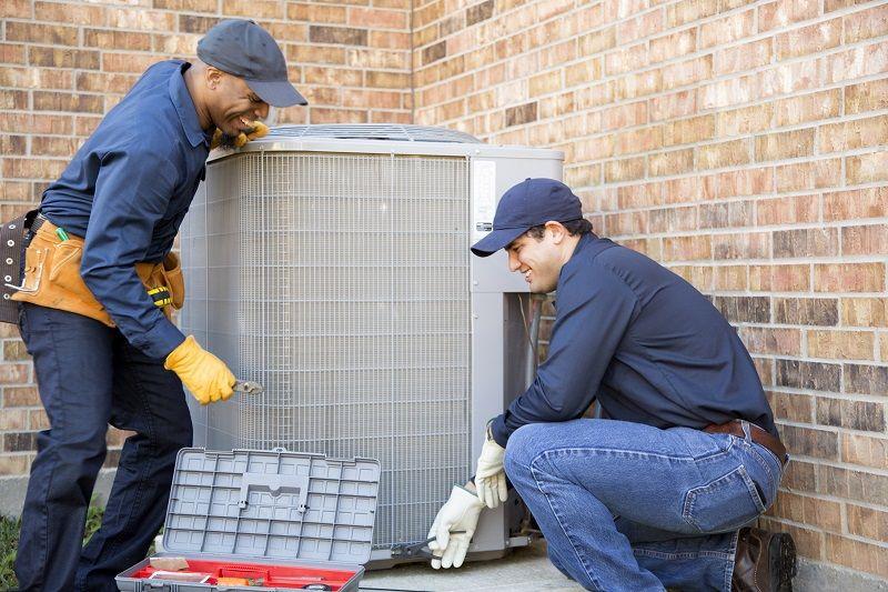 Multi-ethnic-team-of-blue-collar-air-conditioner-repairmen-at-work