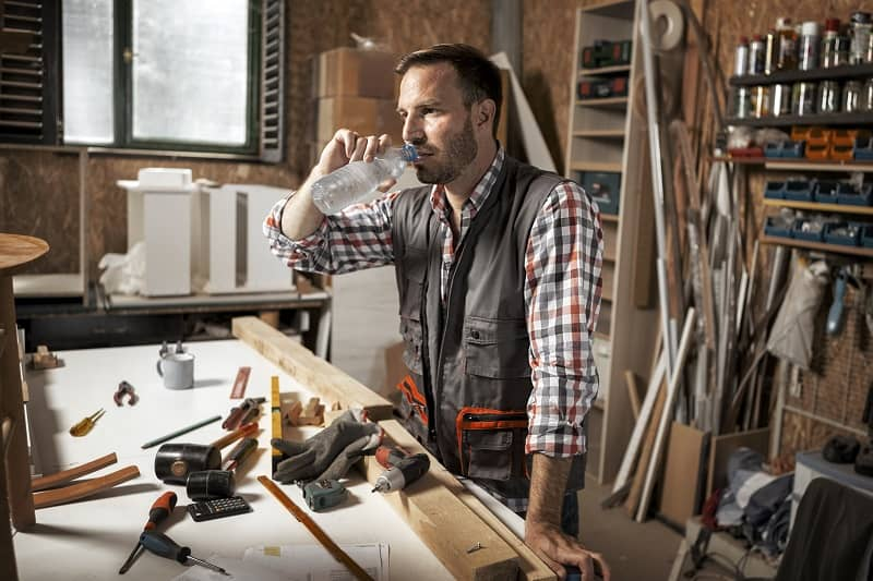 Carpenter craftsman is drinking water taking a break-cm