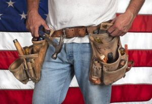 Closeup of carpenter wearing old fashion toolbelt standing in front of American flag -cm
